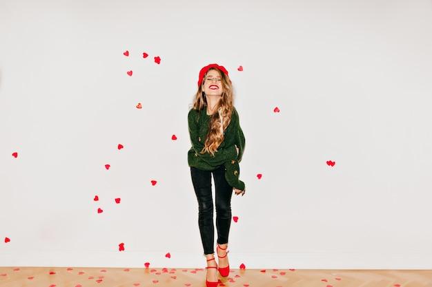白い壁で笑っているかわいいフランスのベレー帽のスリムな笑いの女性