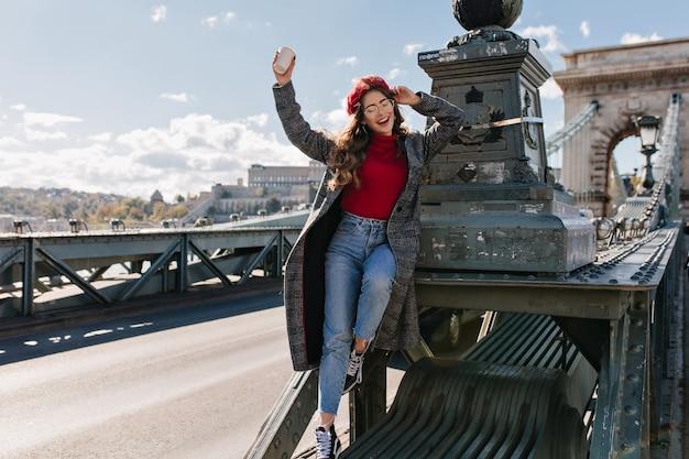 Худенькая смеющаяся женщина в винтажных джинсах позирует на фоне архитектуры в солнечный день в париже