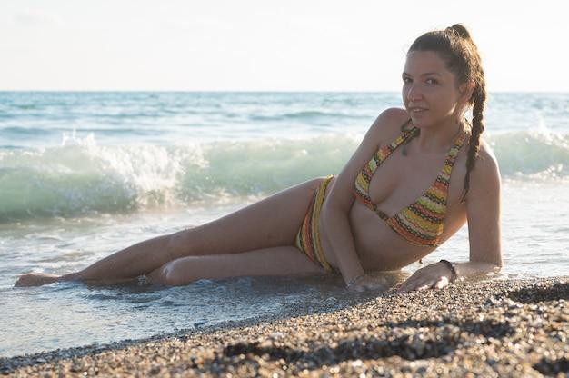 열대 해변에 누워 휴가를 즐기는 여성의 날씬한 다리. 그을린 여성의 발을 씻는 따뜻한 파도.