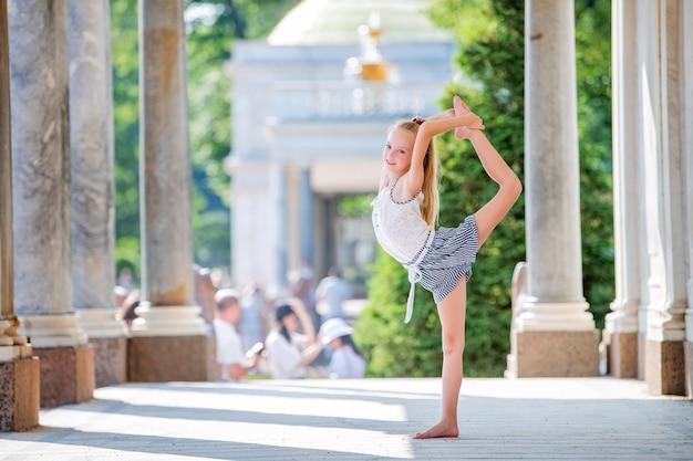 공원의 고풍스러운 건축물을 배경으로 포즈를 취한 날씬한 작은 체조 선수