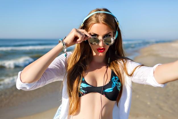 Стройная длинноволосая девушка с бледной кожей делает селфи во время отдыха на морском курорте. открытый портрет счастливой дамы в солнцезащитных очках, слушая музыку и наслаждаясь океанским бризом в выходные.