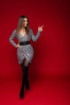Стройная длинноволосая молодая девушка в серебряном праздничном платье показывает