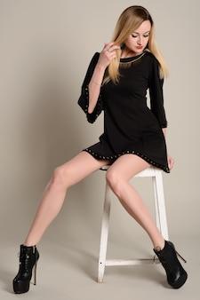 黒のショートドレスとかかとでスリムな長い脚のブロンドの女性が座っています