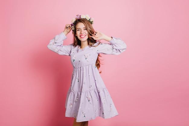 Стройная привлекательная женщина в фиолетовом платье веселится в студии