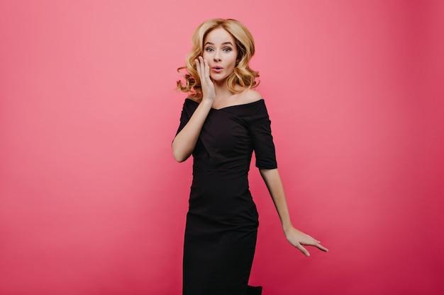 우아한 헤어 스타일 점프와 슬림 사랑스러운 아가씨. 사진 촬영 중에 장난 치는 검은 드레스에 우아한 여성 모델의 사진.