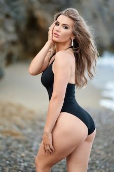 해변에 검은 비키니 입은 슬림 명품 소녀. 뒤에서 찍은 사진. 완벽한 검게 그을린 몸매, 섹시한 엉덩이, 완벽한 몸매.