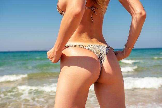 Slim luxury girl in a leopard bikini on the beach.
