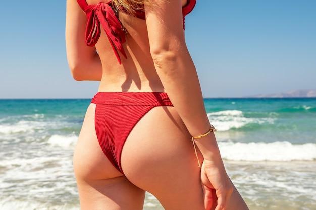 Slim luxury girl in a red bikini on the beach.