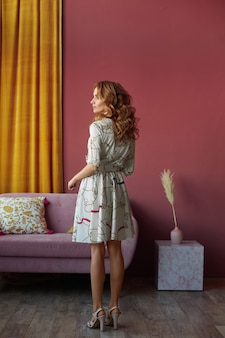 ヴィンテージのインテリアで彼女の背中でポーズをとる流行の夏のドレスを着ている完璧な姿のスリムなモデルの女の子