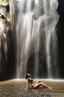 슬림 모델. 활동적인 여행 중 동굴 근처에서 멈춘 수영복을 입은 긍정적인 기뻐하는 여성
