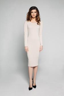 Slim model with brunette wavy hair posing in ivory dress and black heels.
