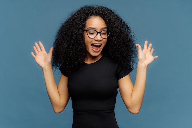 スリムな感情に訴える暗い肌の女性が手を上げ、口を開き、積極的な感情から積極的にジェスチャー