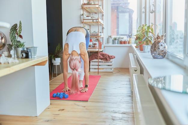 背中に入れ墨のあるスリムなピンクの髪の女性は、自宅でのトレーニングで前屈します