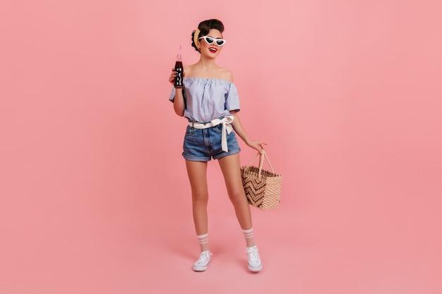 가방을 들고 데님 반바지에 슬림 핀 업 소녀. 분홍색 배경에 음료수를 마시는 매력적인 갈색 머리 아가씨.