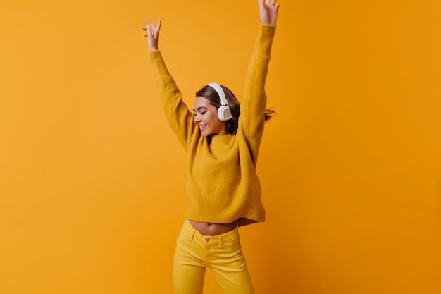 手を上げて踊る黄色いズボンのスリムなポジティブな女性。良い歌を楽しんでいる大きなヘッドフォンで至福の少女の屋内肖像画。