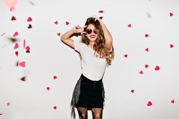 Стройная красивая брюнетка женщина танцует на белой стене