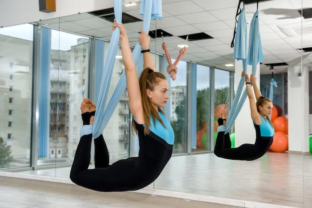 フィットネスジムでフライヨガストレッチ体操をしているスリムなきれいな女性。女性の健康リラックスライフスタイル