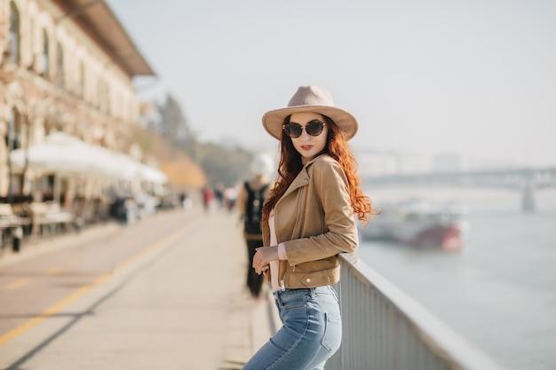 Slim donna dai capelli rossi in cappello alla moda in piedi in posa sicura vicino al mare