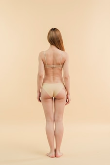 Slim redhead woman with long hair posing in underwear