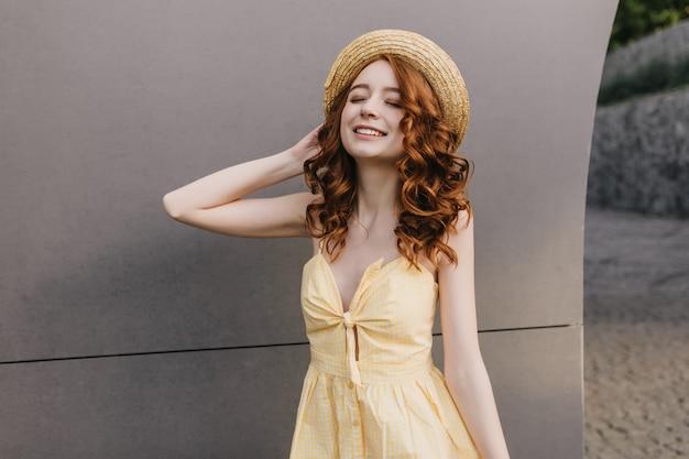 회색 벽에 웃 고 빈티지 드레스에 슬림 로맨틱 소녀. 모자에 백인 생강 여성 모델의 사진입니다.