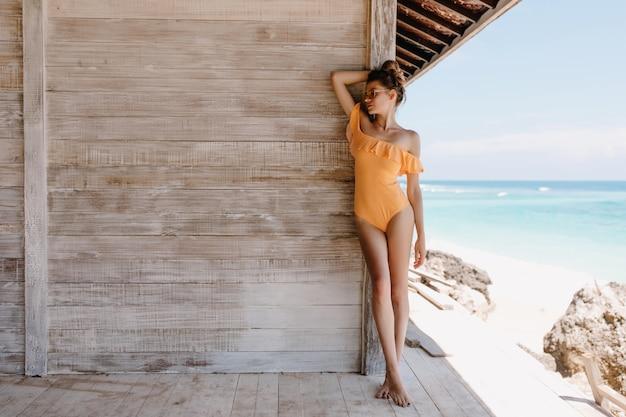 Стройная романтическая девушка в желтых купальниках с удовольствием позирует в выходные на курорте. вдохновленная дама с загорелым телом стоит у деревянного дома.