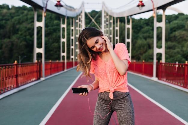 マラソンの前に音楽を聴くスリムなロマンチックな女の子。競争の準備をしている快活な女性の屋外の肖像画。