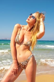 Стройная сексуальная девушка с идеальной фигурой в леопардовом бикини на пляже