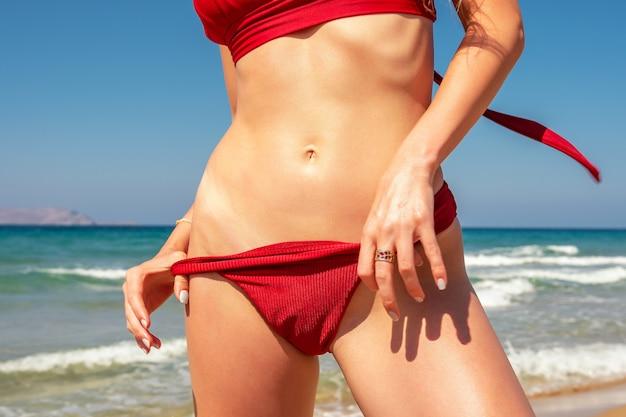 Стройная сексуальная девушка с идеальной фигурой в красном бикини на пляже