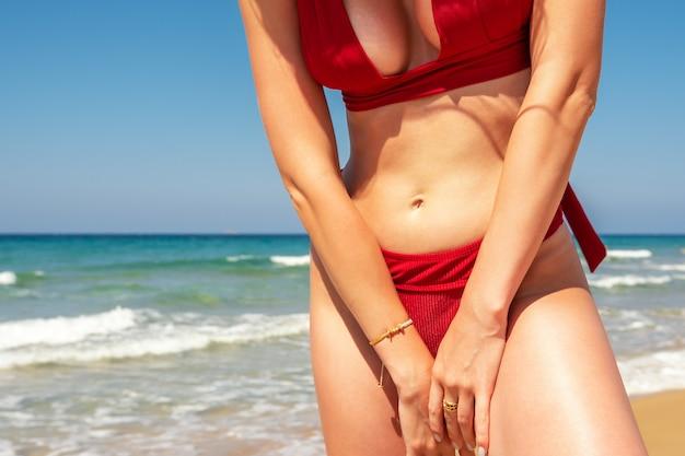 Стройная сексуальная девушка с идеальной фигурой в красном купальнике на пляже.