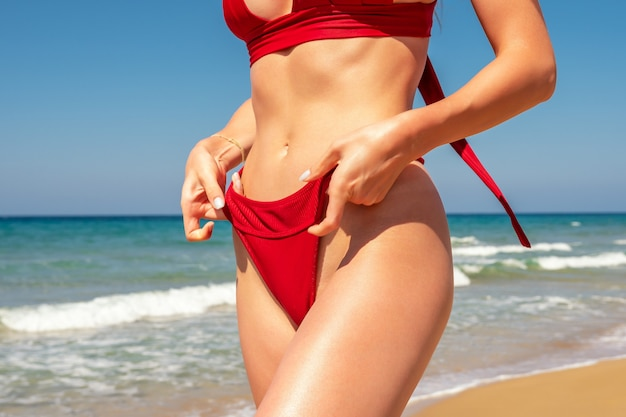 Slim sexy girl with a perfect figure in a red bikini on the beach.