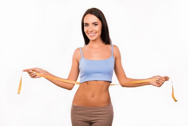 Стройная сексуальная женщина измеряет ее талию сантиметром