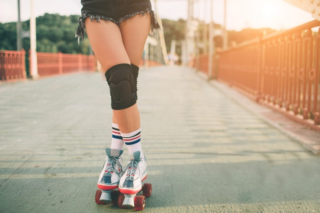Slim and sexy young women and roller skates. summer active vacations in the city. extreme sports