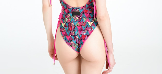 Slim skinny woman buttocks body posing in pink printed swimsuit isolated on white studio
