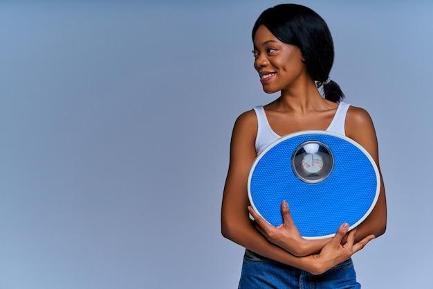 흰색 상단과 청바지에 슬림 웃는 소녀는 무게 기계 사고가 있습니다. 다이어트 개념
