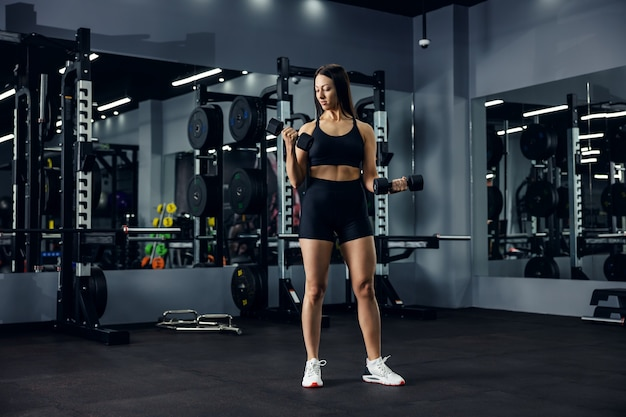 Slim sportswoman in black sportswear doing an exercise with two dumbbells in a dark gym space. fitness sexy girl pumping arms. sports lover, healthy lifestyle