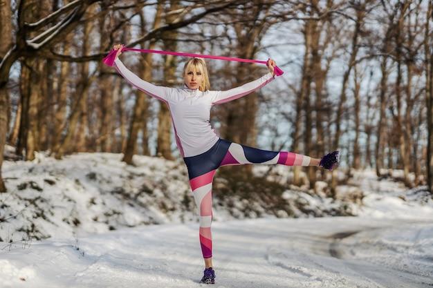 Худенькая спортсменка делает упражнения с силовой резиной, стоя на природе в снежный зимний день.