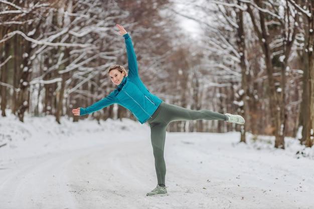 雪の降る天候で自然の中でウォームアップ運動をしているスリムなスポーツウーマン。寒い気温、ウィンタースポーツ、健康的な生活、冬