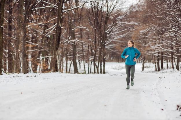 雪の降る天気で自然の中でジョギングするスリムなスポーツウーマン。寒さ、雪、健康的な生活、フィットネス、健康的な習慣