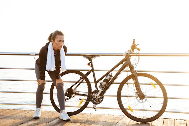 Стройная спортсменка с полотенцем на шее стоит возле велосипеда на открытом воздухе после тренировки на берегу океана