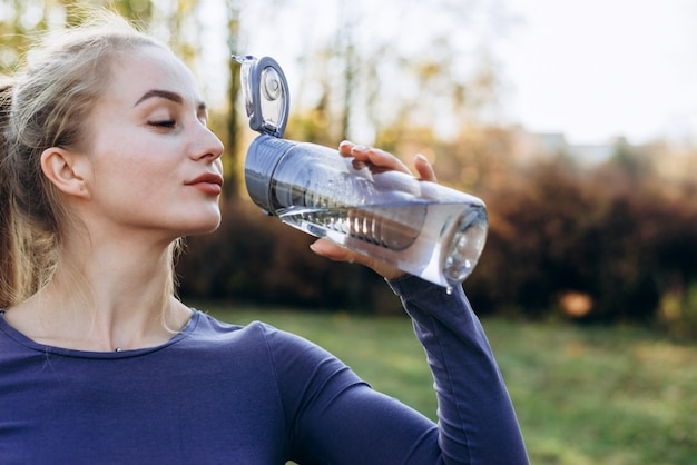 Slim sporty girl drinking water. fitness young woman taking break after training in park.