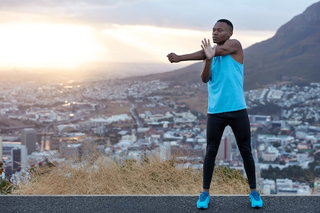 Slim sporty man with strong body, does stretching exercises for hands, prepares for morning run, stands behind mountainous landscape with free space for your promotional content. sport concept