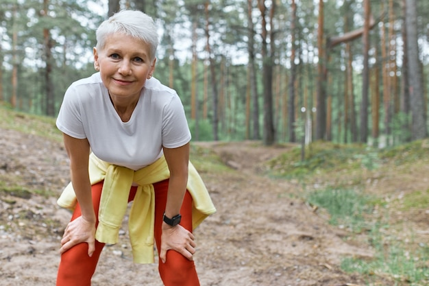 Slim sporty middle aged woman in activewear standing on pine trees background leaning forward