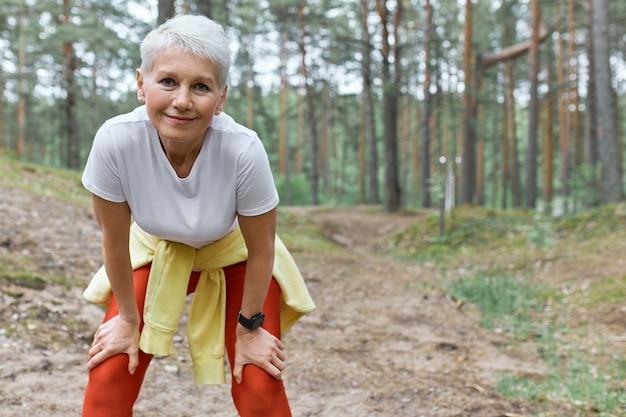 Стройная спортивная женщина средних лет в спортивной одежде стоит на фоне сосен, наклонившись вперед