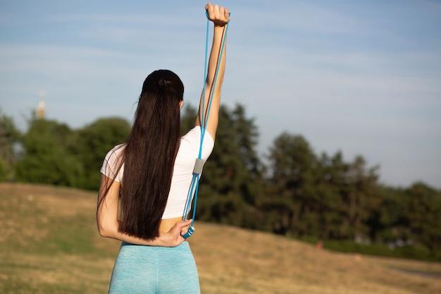 伸縮性のある抵抗バンドでストレッチ運動をしているスリムなスポーティな女性。テキスト用のスペース