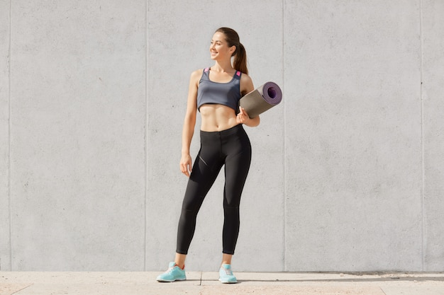 Slim sporty woman holding yoga mat before or after fitness class, stands wearing sportsuit and looking aside
