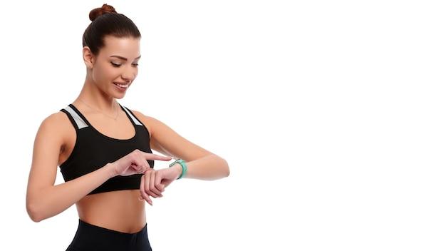 スポーツウェアのスリムで強い白人女性は、白い孤立した背景でスマート時計をチェックします