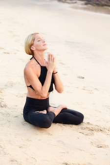 Slim strong mature woman in black practicing yoga on sand beach.