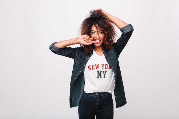アフリカの髪型と赤いマニキュアの時間を過ごすスリムな見事な女の子。喜んでポーズをとるブロンズ肌の素敵な若い女性の屋内の肖像画。