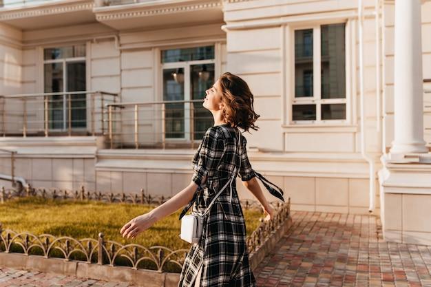 通りを歩いて灰色のドレスを着たスリムな見事な女性。秋の日を楽しんでいる市松模様の服装で熱狂的な巻き毛の女性モデル。