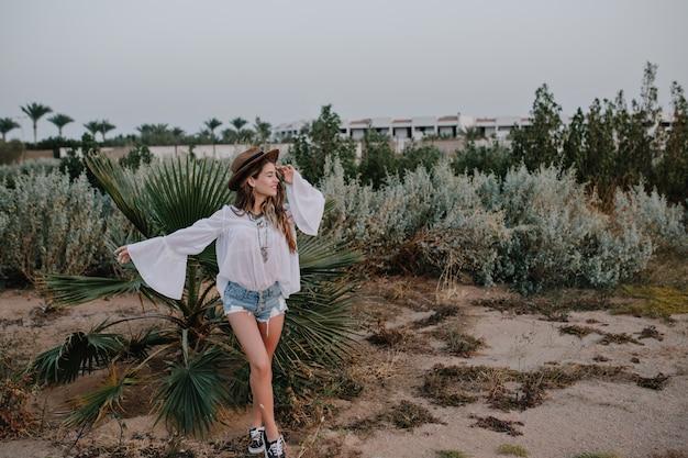 白いブラウスとデニムのショートパンツで外を歩くスリムなスタイリッシュな女性は、エキゾチックな植物と美しい空の景色を楽しんでいます。夢のような表情で喜んでポーズスポーツシューズの魅力的な若い女性